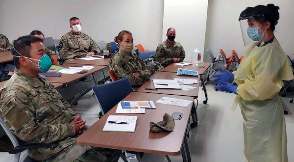 University Hospital integration trainer and Registered Nurse Helena Quezon shows the wear, removal and disposal of personal protective equipment during integration training to Urban Augmentation Medical Task Force-627 Soldiers at University Hospital in San Antonio July 8.