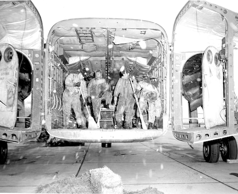 "Airmen sweep up a C-119 aircraft after a ""mercy mission"" that involved dropping hay"