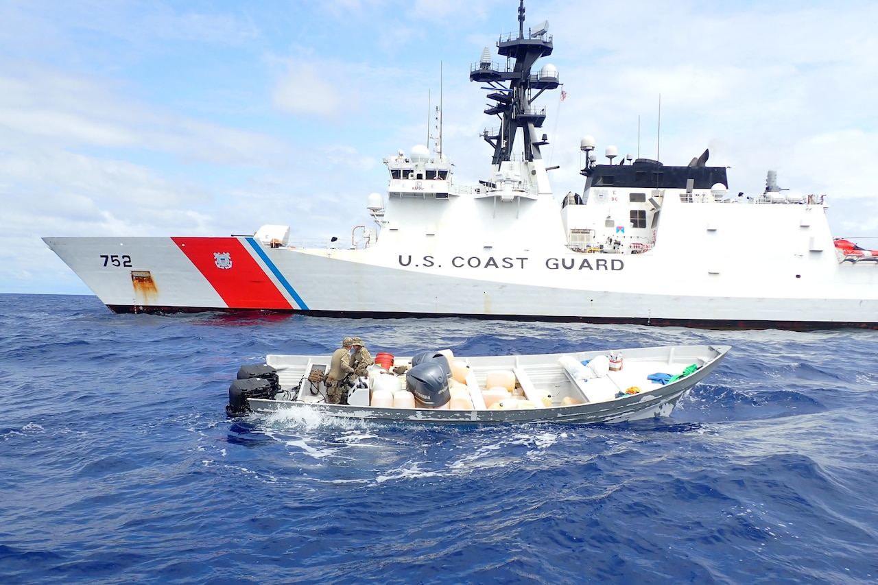 Service members search a small boat.