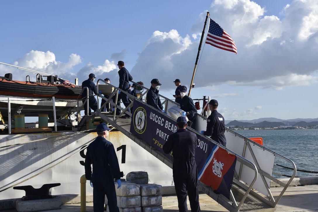 Service members bring seized drugs off cutter.