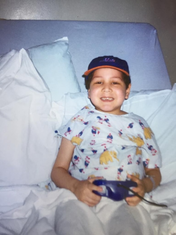 Airman 1st Class Isaiah A. Nieves, 2nd Maintenance Squadron aerospace ground equipment journeyman, plays video games in a hospital bed as a child. Nieves was diagnosed with Acute Lymphoblastic Leukemia at the age of four. (Courtesy photo)