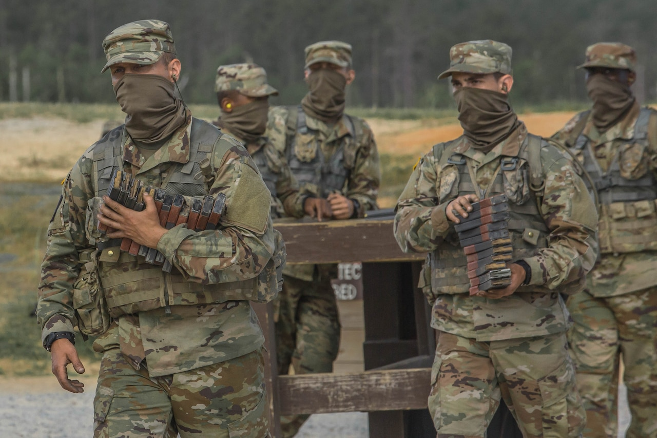 Service members in uniform and wearing face masks carry ammunition magazines.