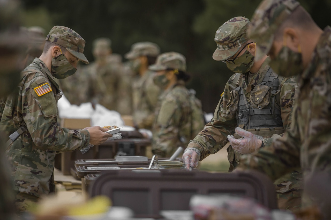 Service members wearing face masks gather around an outdoor table with portable meal containers.