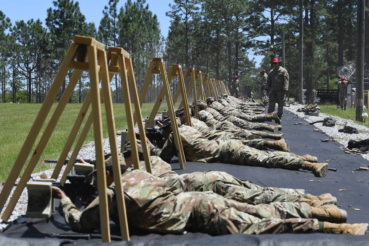 Service members lay on the ground and aim their rifles downrange.