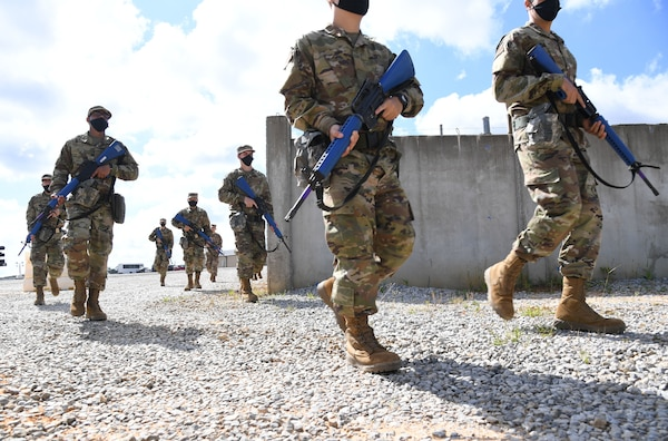 Service members walk on gravel carrying blue training rifles.