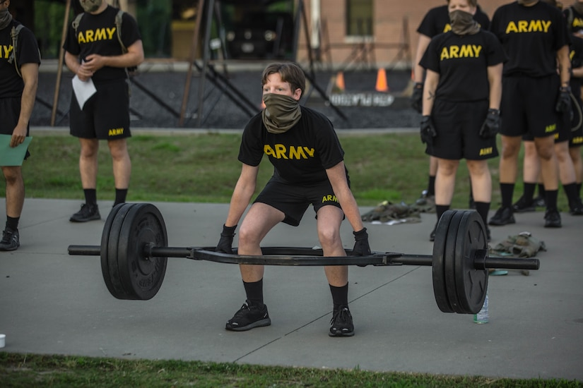 A service member lifts a barbell; others wait nearby.