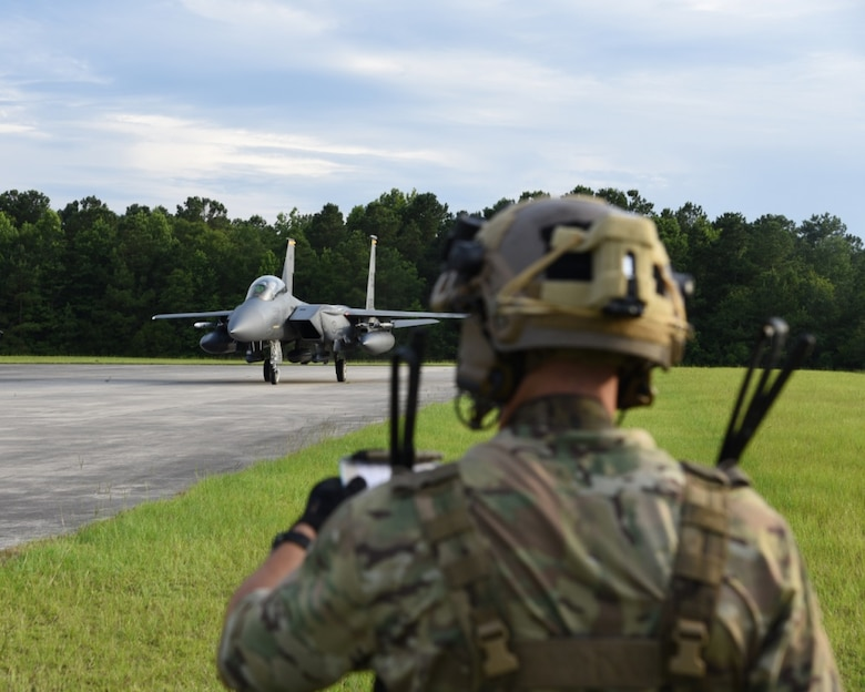 An Air Force Special Tactics operator helps secure an airfield for an F-15 fighter aircraft during a Forward Air Refueling Point training mission