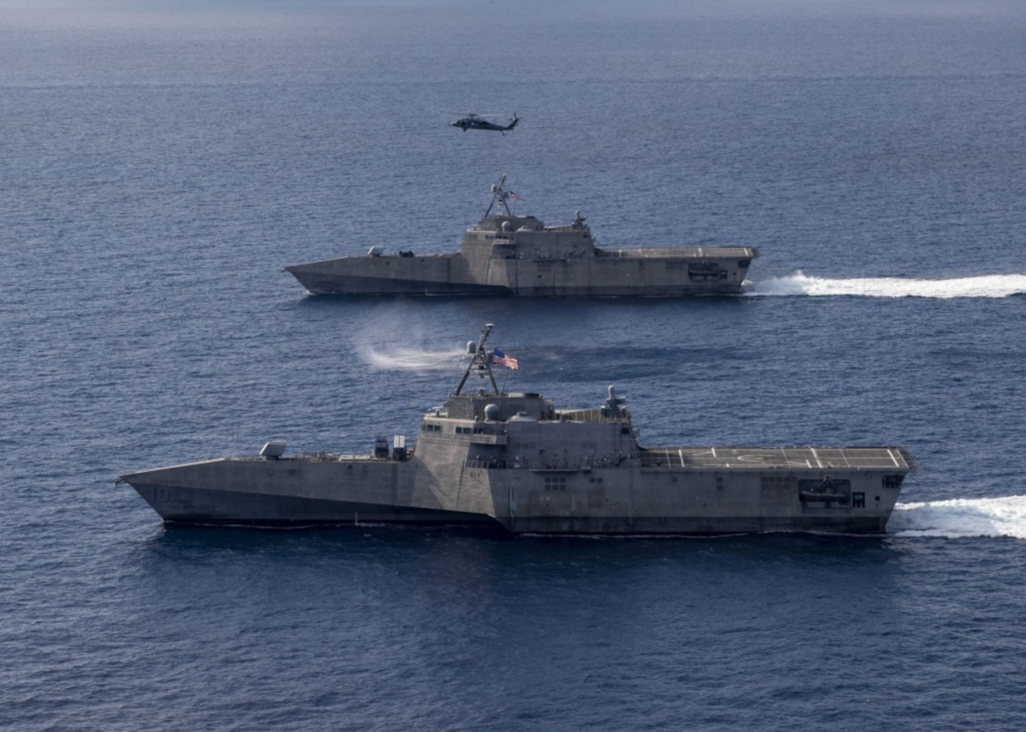SOUTH CHINA SEA (Jan. 28, 2020) The Independence-variant littoral combat ships USS Gabrielle Giffords (LCS 10), bottom, and USS Montgomery (LCS 8) operate in the South China Sea, accompanied by an MH-60S Sea Hawk of Helicopter Sea Combat Squadron (HSC) 23, Jan. 28, 2020. Montgomery and Gabrielle Giffords are on rotational deployments to USINDOPACOM, conducting operations, exercises and port visits throughout the region and working hull-to-hull with allied and partner navies to provide maritime security and stability, key pillars of a free and open Indo-Pacific.