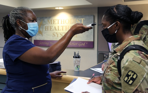 Sheryl Rudolph, registered nurse and Director of Education at Methodist Hospital San Antonio, takes the temperature of U.S. Army Capt. Terry Villas