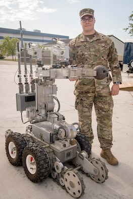 Senior Airman Stephan Wojciechowski, 434th Civil Engineer Squadron explosives ordnance disposal technician, poses with an Air Force medium sized robot holding a civil war era cannon ball at Grissom Air Reserve Base, Indiana, July 12, 2020. Wojciechowski and a team of four other EOD specialists were sent to the Berrien Springs County Plaza Museum Berrien Springs, Michigan, June 18, when a new employee discovered multiple munitions, one with the message 'danger, might be active' attached to a post-it note.  (U.S. Air Force photo/Master Sgt. Ben Mota)