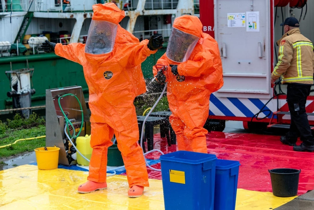 U.S Army Reserve Staff Sgt. William Haynes, survey team member with the 773rd Civil Support Team, 7th Mission Support Command, right, decontaminates fellow team member Sgt. Jonathan Medina with the Dutch Fire Department's decontamination system during a training exercise in Gravendeel, Netherlands, July 8, 2020. The one-day CBRN situational training exercise focused on a CBRN incident on a maritime vessel at the Dutch Harbor in Gravendeel, Netherlands.  (Photo by Netherlands Captain Tom Martens)