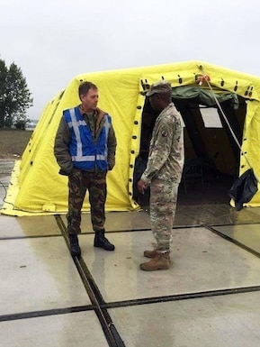 U.S Army Reserve Maj. Ralph Scott, commander of the 773rd Civil Support Team, 7th Mission Support Command, right, shares tactics, techniques and procedures with Netherlands Maj. Rens, commander of the CBRN Response Unit, during a training exercise in Gravendeel, Netherlands, July 8. The one-day CBRN situational training exercise focused on a CBRN incident on a maritime vessel at the Dutch Harbor in Gravendeel, Netherlands.  (U.S Army Reserve Photo by 1st Sgt. Domenic Barbeiro).
