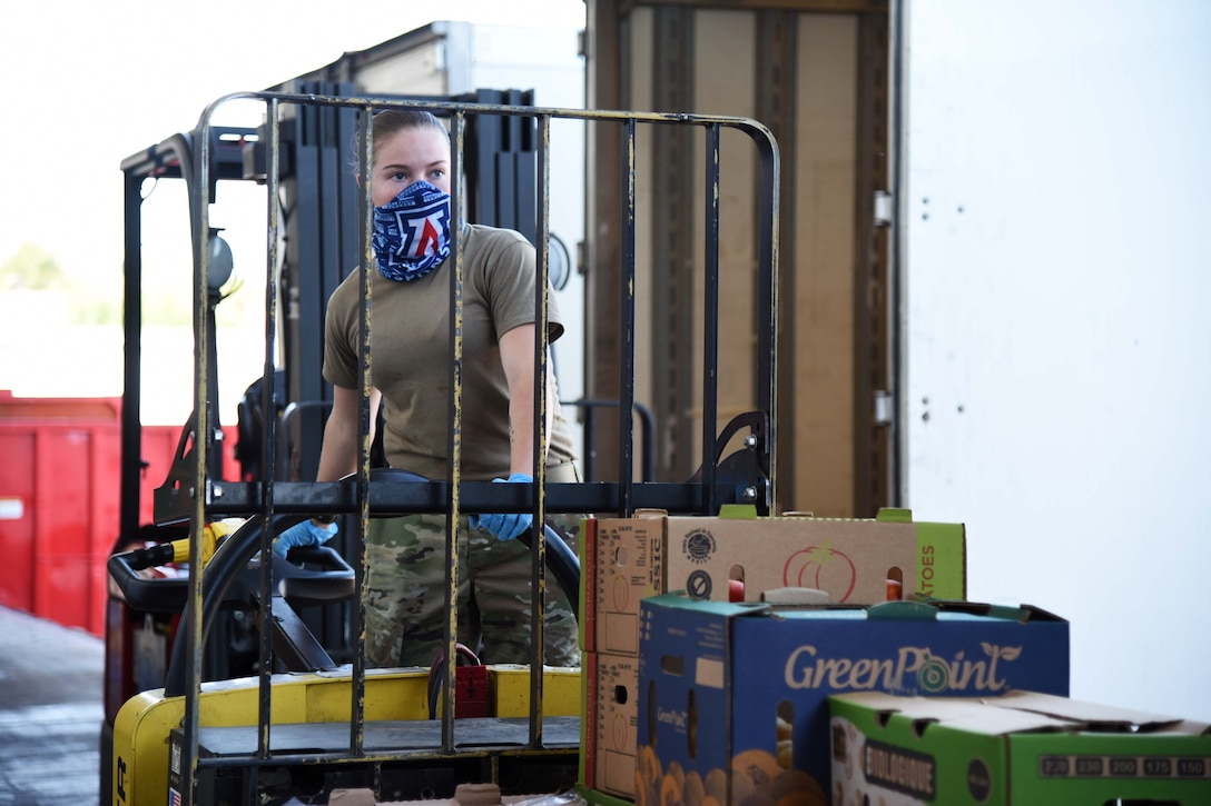 A service member wearing a mask drives a forklift.