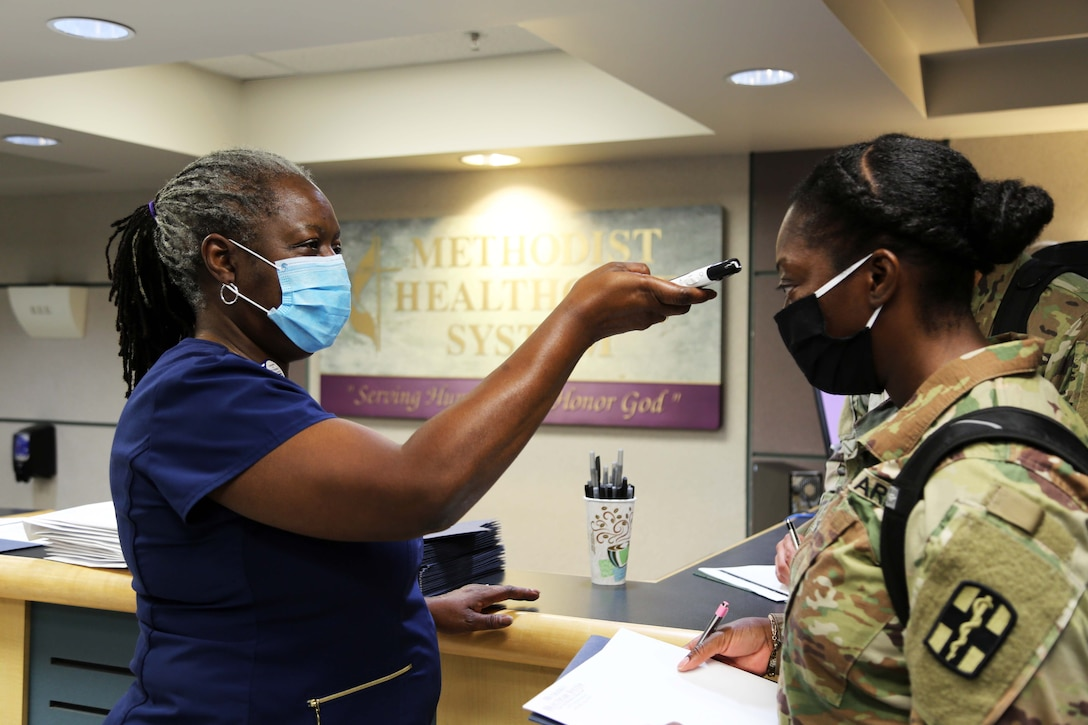 A nurse wearing a mask takes the temperature of a service member wearing a mask.