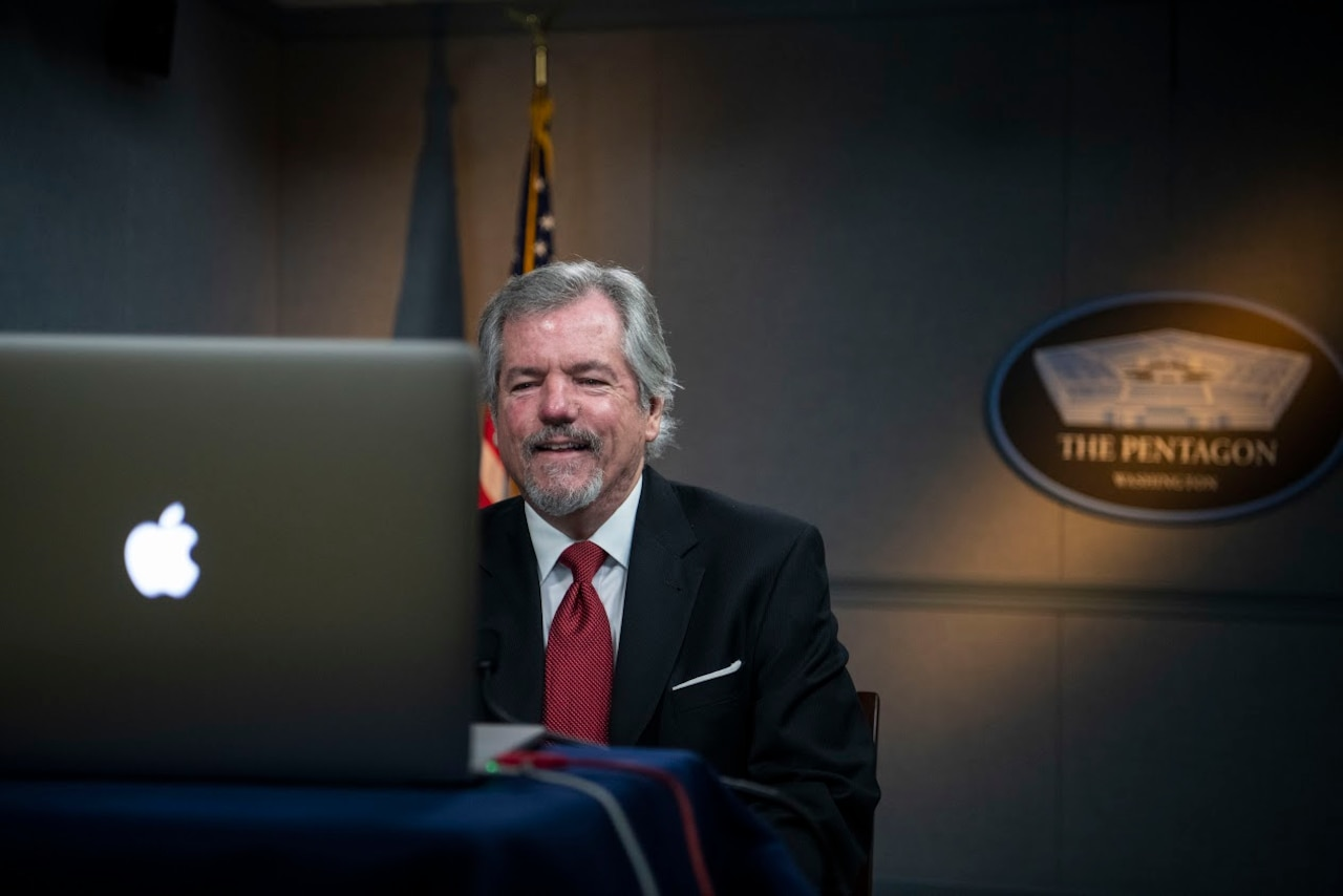 A man sits at a computer while a Pentagon sign hangs behind him.