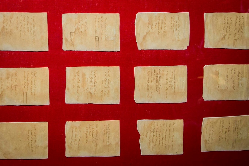 Cigarette papers are displayed on a red background.