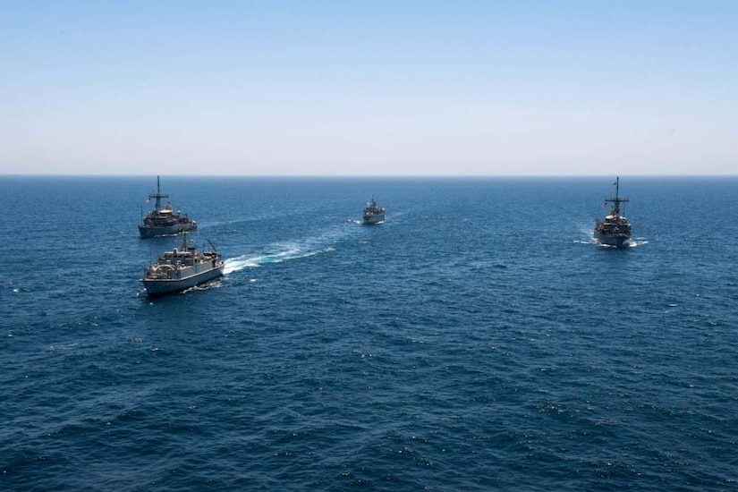 Four ships moves across the ocean.