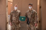 Spc. Cameron Kerkes is presented an Army Achievement Medal on July 7, 2020, for earning the U. S. Army Central's Paralegal of the Quarter competition for the 3rd quarter of 2020. The AAM is presented by Kerkes' sponsor for the competition, Sgt. Joshua Snyder while they are both deployed to the Middle East with the Headquarters & Headquarters Company, 2-147th Assault Helicopter Battalion, 34th Expeditionary Combat Aviation Brigade. (U.S. Army photo by Sgt. Sydney Mariette)