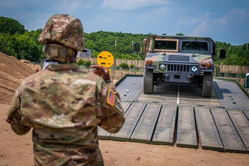 A soldier guides a Humvee across a bridge.