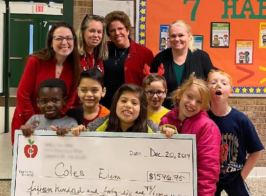 Four women and six school children pose with a check presented to Coles Elementary School in Manassas, Va., Dec. 20, 2019.