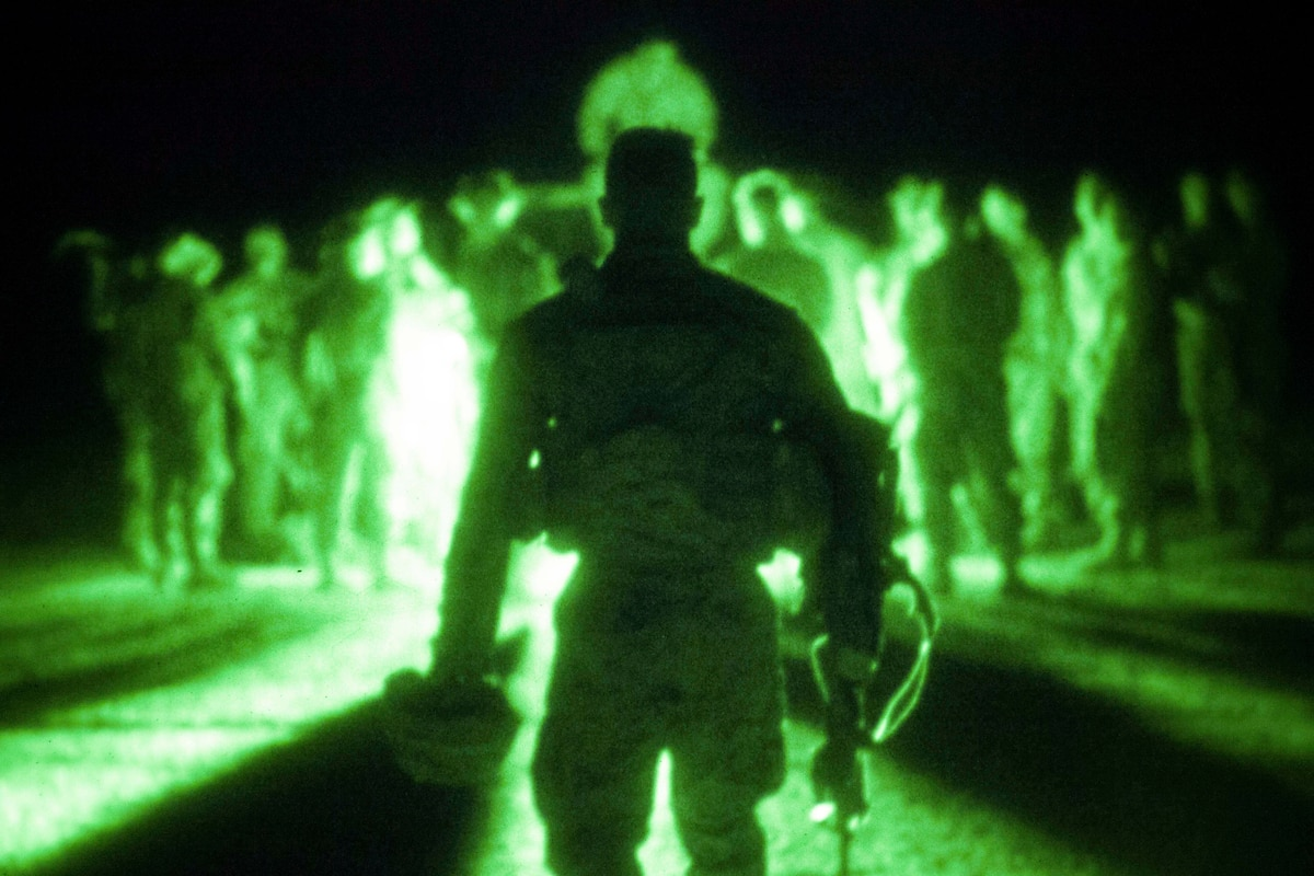 Marines stand together illuminated by a green light.