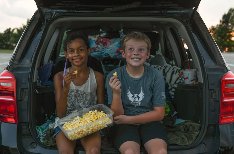 Team Whiteman children eat popcorn during a Base Community Council hosted drive-in movie event, at the Mission's End Club on Whiteman Air Force Base, Missouri, July 11, 2020. The BCC hosted the movie night to thank all the military spouses for the service and commitment that comes with being married to a military member. (U.S. Air Force photo by Staff Sgt. Sadie Colbert)