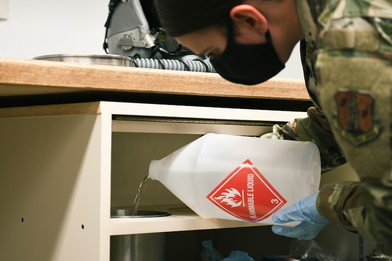 Airman fills container with isopropyl alcohol