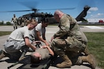 Airmen and Soldiers from the Indiana National Guard prepare to load a patient into a UH-60 Black Hawk helicopter during a medical transport exercise at the Johnson County Armory, Franklin, July 2, 2020. During the exercise, members practiced loading and unloading procedures via voice direction with the aircraft off and using hand signals with the aircraft engines running. Due to rotor wash, aka propeller wash, service members did not wear masks for safety reasons as the masks could cause debris interfering with helicopter propellers. (U.S. Air National Guard photo by Staff Sgt. Justin Andras)