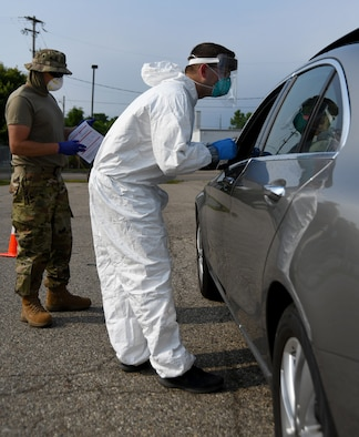 A member of the Michigan Air National Guard prepares to administer a COVID-19 test during drive-thru testing in Flint, Mich., July 10, 2020. The Michigan National Guard has partnered with a variety of state agencies to provide free tests to Michigan residents.