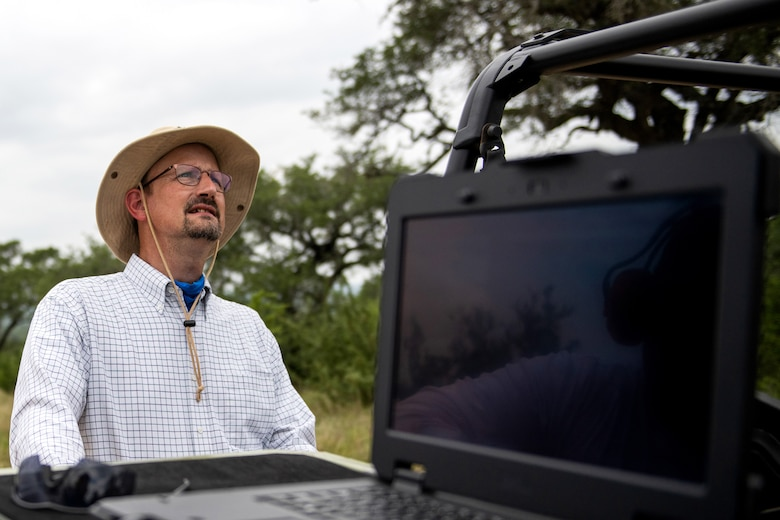 Paul Jurena, Air Force Civil Engineer Center natural resources specialist, watches as an unmanned aerial system flies during a test flight July 9, 2020, at Joint Base San Antonio-Camp Bullis, Texas.