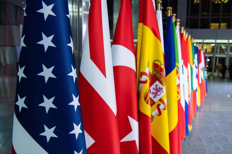 A row of flags stand in a lobby-like room.