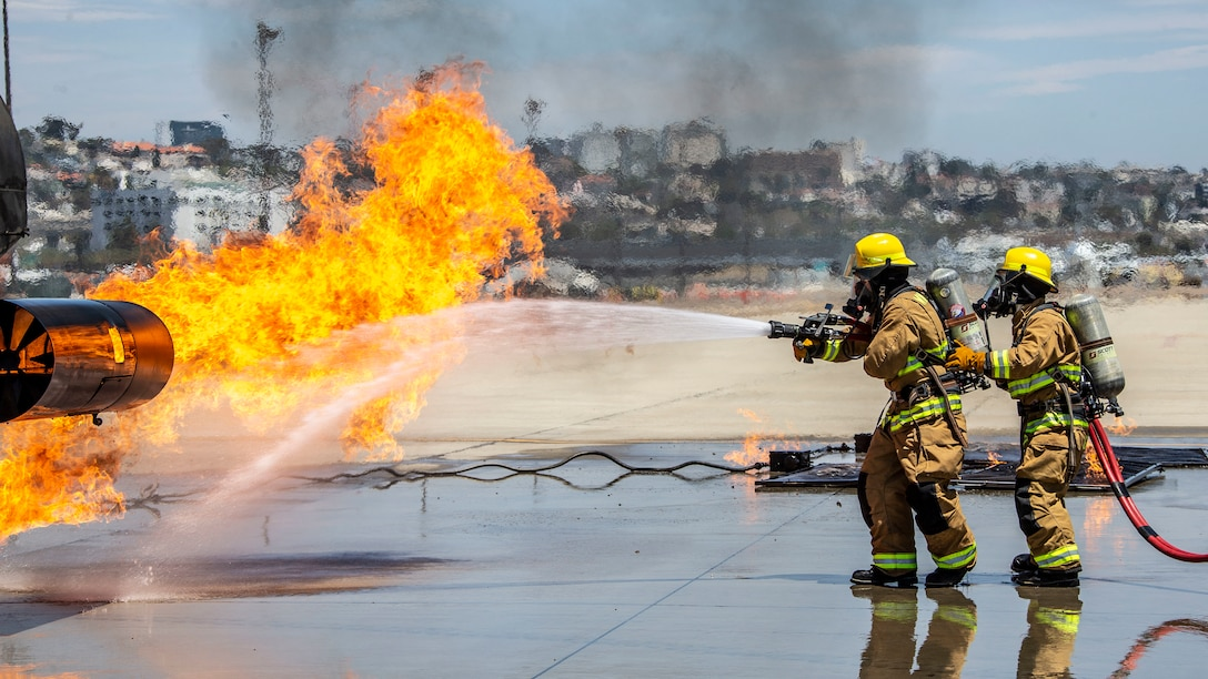 U.S. Marines work with firefighters from around San Diego County to put out a fire on a mobile aircraft firefighting trainer during a training evolution at the San Diego International Airport in San Diego, July 10.