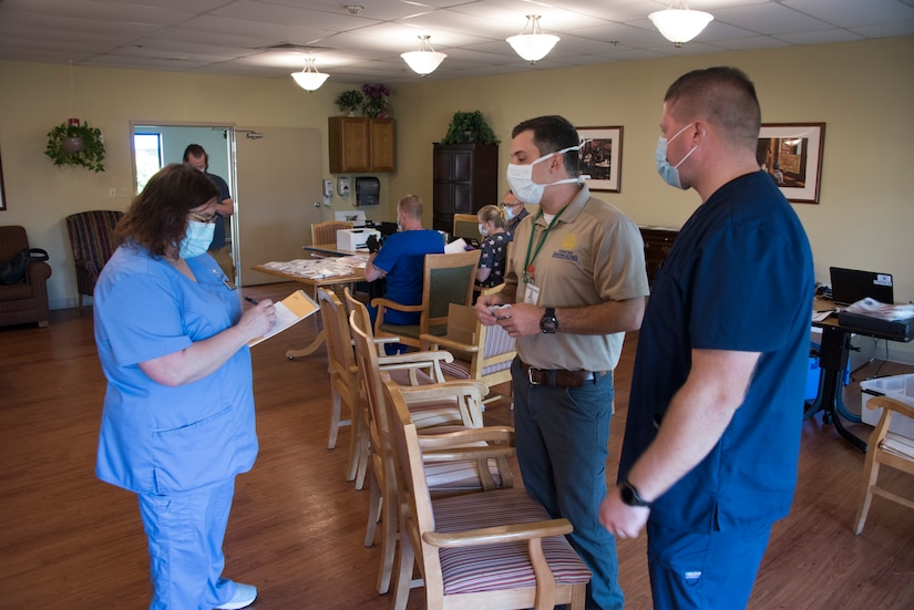 A nurse holding a clipboard speaks with two men. All are wearing face masks.