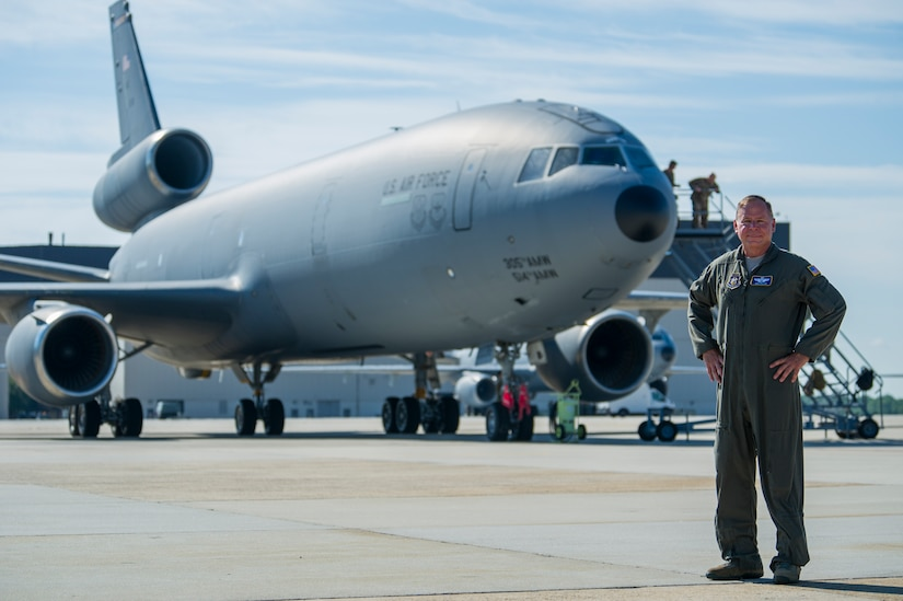 Photo of an Airman posing in front of a KC-10 aircraft.