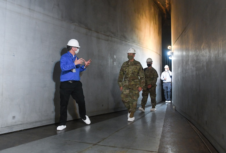 Scott Meredith, left, technical advisor for Arnold Engineering Development Complex (AEDC) Flight Systems Branch, talks about the 16-foot supersonic wind tunnel as he, Chief Master Sgt. Stanley Cadell, second from left, command chief, Air Force Materiel Command, and others, walk through the flexible nozzle of the tunnel, July 8, 2020, at Arnold Air Force Base, Tenn., headquarters of AEDC. The visit to the Base by Cadell and Gen. Arnold W. Bunch Jr., commander, Air Force Materiel Command, focused on COVID-19 response and diversity and inclusion. (U.S. Air Force photo by Jill Pickett) (This image has been altered by obscuring a badge for security purposes.)