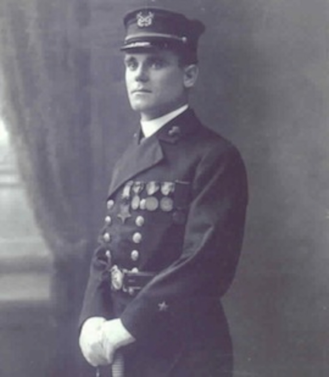 A man in a uniform stands for a photo.
