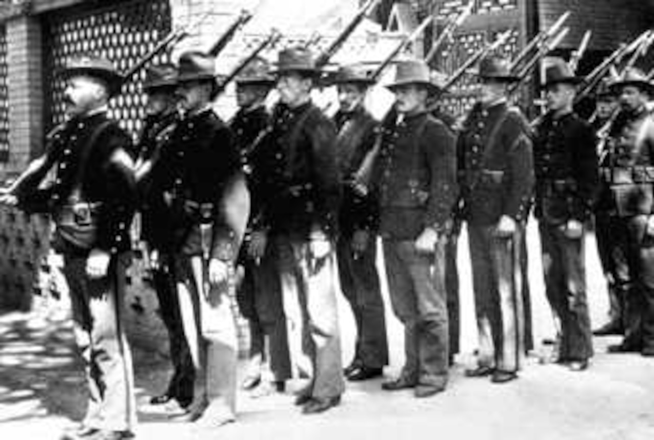 Men with rifles over their shoulders stand in line and at attention.