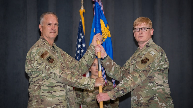 Col. Christopher Hudson, right, outgoing 2nd Medical Group commander, relinquishes the guidon to Col. Michael A. Miller, left, 2nd Bomb Wing commander, during a change of command ceremony at Barksdale Air Force Base, La., July 10, 2020. The passing of the guidon symbolizes a transfer of command.