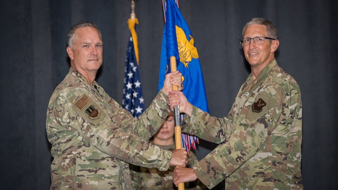 Col. Erich W. Schroeder, right, incoming 2nd Medical Group commander, receives the guidon from Col. Michael A. Miller, left, 2nd Bomb Wing commander, during a change of command ceremony at Barksdale Air Force Base, La., July 10, 2020. The passing of the guidon symbolizes a transfer of command.