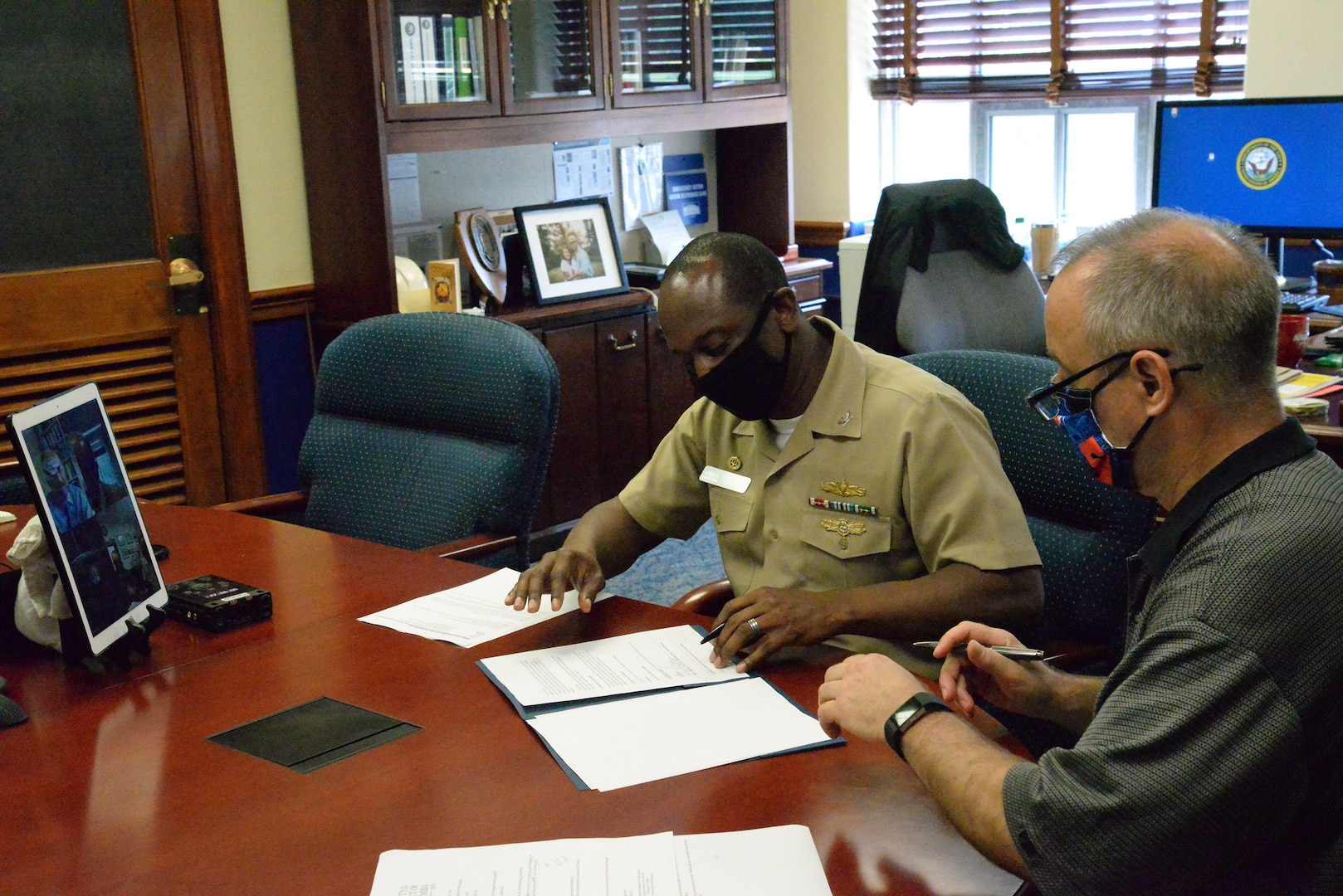 Capt. Cedric McNeal, commanding officer of Naval Surface Warfare Center, Carderock Division, and Technical Director Larry Tarasek sign an Education Partnership Agreement from their office in West Bethesda, Md.