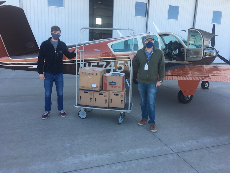 Two men with supplies in front of an airplane