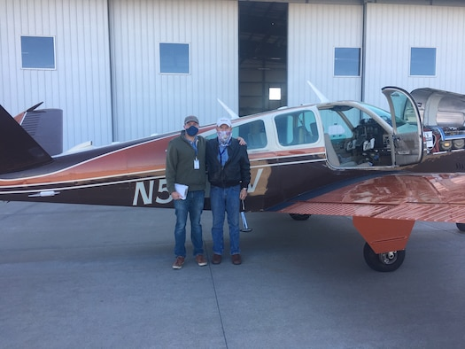 Two men posing in front of airplane