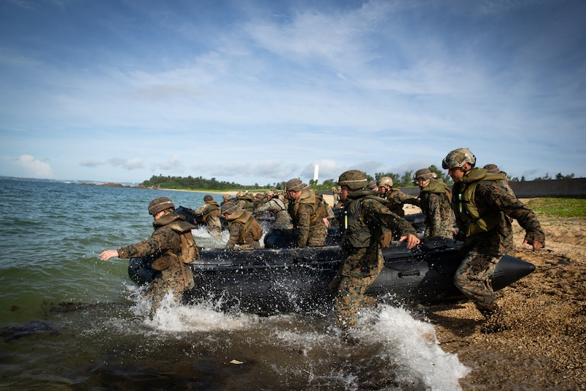 A group of Marines carry a rubber craft into the water.