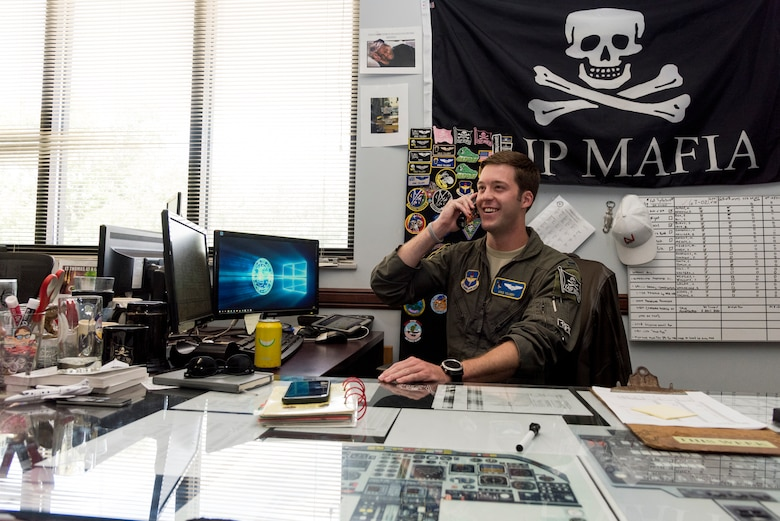 """First Lt. Kristopher Tillery, 86th Flying Training Squadron instructor pilot, makes a phone call at the office, June 25, 2020 at Laughlin Air Force Base, Texas. Lt. Col. Shawn Chaney, 86th FTS director of operations, said, """"It's been amazing seeing our squadron balance quarantine and COVID-19 prevention, while pushing forward with the mission; we're becoming better through this."""" (U.S. Air Force photo by Senior Airman Anne McCready)"""