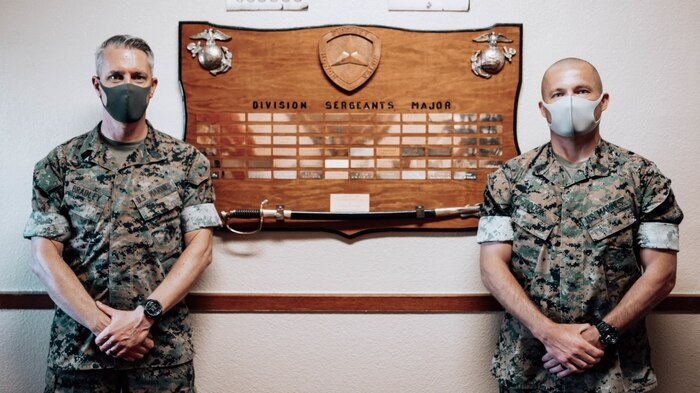 """U.S. Marine Corps Sgt. Maj. Dennis M. Bradley (left) and Sgt. Maj. Eric D. Cook stand in front of the """"Division Sergeants Major"""" board in the 3rd Marine Division Headquarters building on Camp Courtney, Okinawa, Japan, July 13, 2020. This traditional board captures the lineage of the senior enlisted leaders who have carried the title of Division Sergeant Major. Bradley will transfer the title to Sgt. Maj. Cook on July 15 without a ceremony to avoid formations or large gatherings, therefore lowering the chances to spread COVID-19. (U.S. Marine Corps photo by Cpl. Josue Marquez)"""