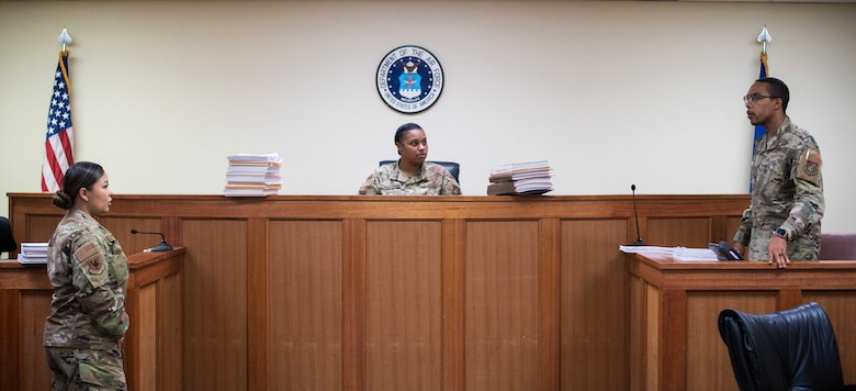 Airman from the 18th Wing Office of the Staff Judge Advocate roleplay a case in the court room.