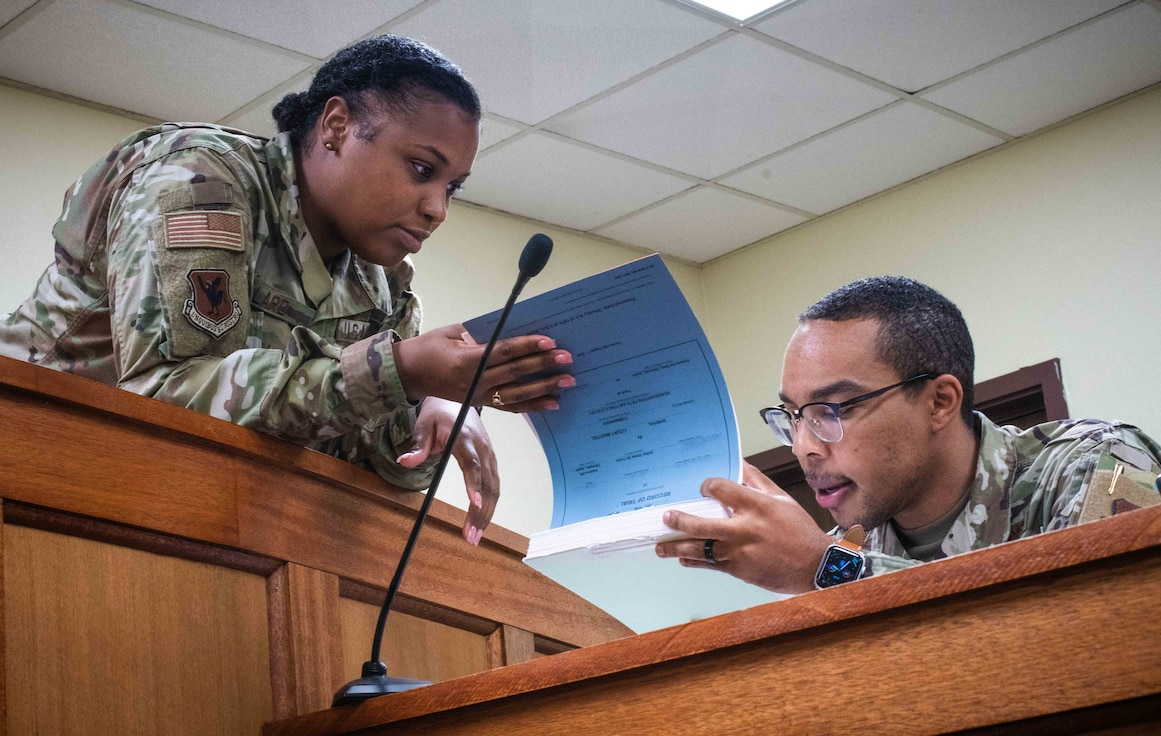 Airman from the 18th Wing Office of the Staff Judge Advocate review case files in the court room at Kadena Air base.
