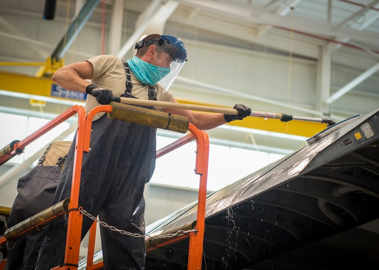Airman 1st Class A.J. Raffles, 103rd Maintenance Squadron structural maintenance specialist, scrubs the wing of a C-130H Hercules during an aircraft wash at the Bradley Air National Guard Base fuel cell and corrosion control facility in East Granby, Connecticut, July 13, 2020. Each of the 103rd Airlift Wing's eight C-130 aircraft are washed every six months to clean contaminants and prevent corrosion, ensuring aircraft readiness and extending its life cycle. (U.S. Air National Guard photo by Staff Sgt. Steven Tucker)