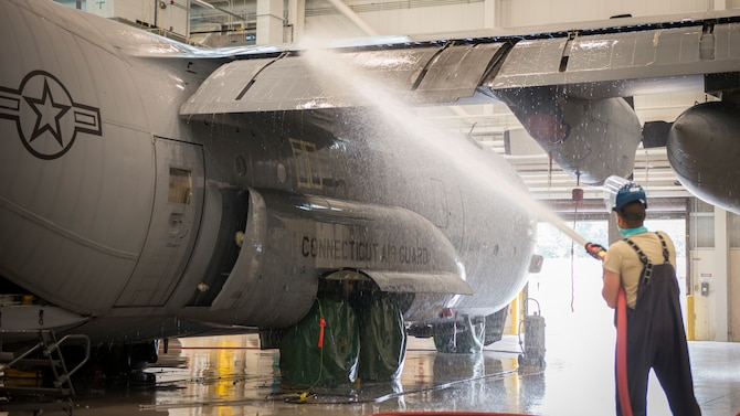 Airman 1st Class A.J. Raffles, 103rd Maintenance Squadron structural maintenance specialist, washes a C-130H Hercules at the Bradley Air National Guard Base fuel cell and corrosion control facility in East Granby, Connecticut, July 13, 2020. Each of the 103rd Airlift Wing's eight C-130 aircraft are washed every six months to clean contaminants and prevent corrosion, ensuring aircraft readiness and extending its life cycle. (U.S. Air National Guard photo by Staff Sgt. Steven Tucker)