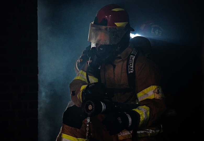A U.S. Air Force firefighter assigned to the 48th Civil Engineering Squadron extinguishes a fire inside the structural training facility during a controlled burn training exercise at Royal Air Force Lakenheath, England, July 8, 2020. Structural training exercises allow Liberty Wing firefighters to improve communication and teamwork in low visibility, high stress environments. (U.S. Air Force photo by Airman 1st Class Jessi Monte)